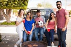 Groupe d'amis traînant à un jeu de football Photo libre de droits
