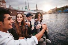 Groupe d'amis traînant par le lac avec des boissons Photos stock
