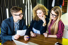 Groupe d'amis travaillant à leur bureau moderne de petite entreprise Exposition d'homme sur son avis sur le carnet Image libre de droits
