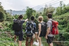 Groupe d'amis trimardant par une jungle Photos libres de droits