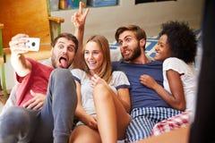 Groupe d'amis utilisant des pyjamas prenant Selfie sur le mobile Images libres de droits