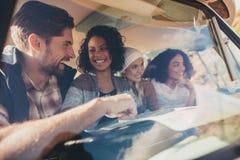 Groupe d'amis voyageant dans un fourgon avec la carte Images stock