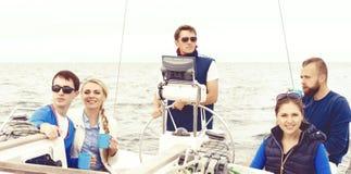 Groupe d'amis voyageant sur un yacht, appréciant une bonne journée d'été et buvant d'un thé Photographie stock libre de droits