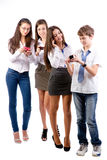 Groupe d'années de l'adolescence utilisant des téléphones portables Photo libre de droits