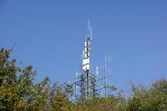 Groupe d'antennes sur la tour sur la colline Photos stock