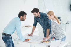 Groupe d'architectes discutant des plans dans le bureau moderne photos stock