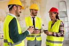 Groupe d'architectes parlant sur la pause-café au chantier de construction image stock