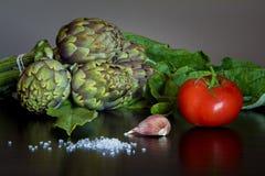 Groupe d'artichauts avec la tomate, le clou de girofle d'ail et le sel brut photographie stock