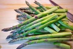 Groupe d'asperge ou de spargel fraîche verte en allemand du plat choping avec le couteau de cuisine Photos libres de droits