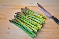 Groupe d'asperge ou de spargel fraîche verte en allemand du plat choping avec le couteau de cuisine Image libre de droits