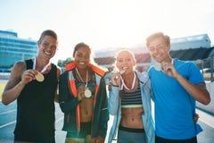 Groupe d'athlètes avec des médailles d'or semblant heureuses Photographie stock