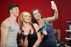 Groupe d'athlètes prenant le selfie avec des haltères au centre de fitness Photographie stock libre de droits