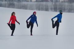 Groupe d'athlètes réchauffant et s'étirant avant exercice dans la forêt d'hiver images libres de droits