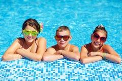 Groupe d'enfants adolescents heureux dans la piscine Image stock