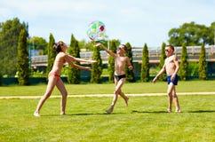 Groupe d'enfants adolescents jouant avec la boule l'été Image stock
