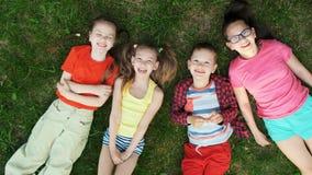 Groupe d'enfants allongés sur l'herbe clips vidéos