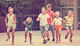 Groupe d'enfants amicaux courant ensemble dans la ville l'été Image stock