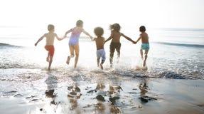 Groupe d'enfants appréciant leur temps à la plage photos stock