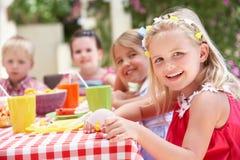 Groupe d'enfants appréciant la réception de thé extérieure Photo stock