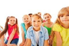 Groupe d'enfants attentifs s'asseyant et souriant Photos stock