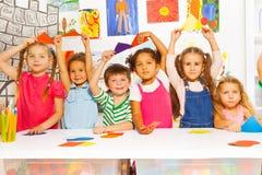 Groupe d'enfants avec des formes de carton de triangle Photographie stock libre de droits