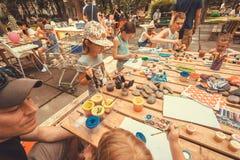 Groupe d'enfants avec des parents jouant avec des peintures et des crayons sur la table du terrain de jeu de ville Images stock