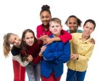 Groupe d'enfants avec l'embrassement différent de teint Image stock