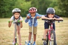 Groupe d'enfants avec le vélo et le scooter Photo stock