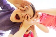 Groupe d'enfants ayant l'amusement et faisant des visages dehors Photo libre de droits