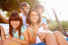 Groupe d'enfants ayant l'amusement sur l'oscillation dans le terrain de jeu Photographie stock