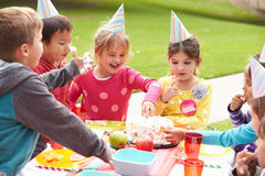 Groupe d'enfants ayant la fête d'anniversaire extérieure Image stock