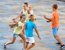 Groupe d'enfants courant dehors dans la rue de ville Photographie stock