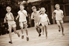 Groupe d'enfants courant dehors dans la rue de ville Photos libres de droits