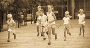 Groupe d'enfants courant dehors dans la rue de ville Image libre de droits