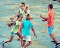 Groupe d'enfants courant dehors dans la rue de ville Image stock