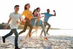Groupe d'enfants courant sur la plage Images stock