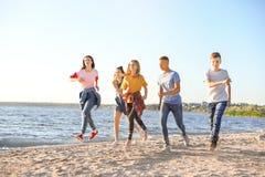 Groupe d'enfants courant sur la plage Photo stock