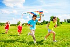 Groupe d'enfants courus avec le cerf-volant images stock