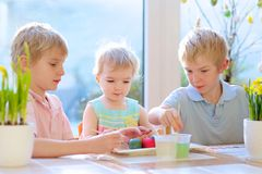 Groupe d'enfants décorant des oeufs de pâques Photos libres de droits