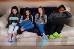 Groupe d'enfants désengagés et ennuyés sur des périphériques mobiles Image stock