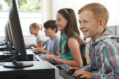 Groupe d'enfants d'école primaire dans la classe d'ordinateur images stock