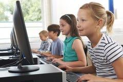 Groupe d'enfants d'école primaire dans la classe d'ordinateur Images libres de droits