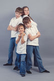 Groupe d'enfants dans des jeans sur le backgroud gris Photo stock