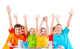 Groupe d'enfants dans des T-shirts colorés avec les mains augmentées Image libre de droits