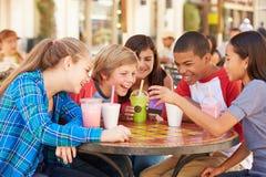 Groupe d'enfants dans le ½ de CafÅ regardant le texte au téléphone portable Images stock