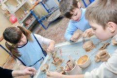 Groupe d'enfants dans le studio de poterie Images stock