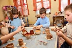 Groupe d'enfants décorant leur poterie d'argile Photos stock