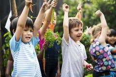 Groupe d'enfants de jardin d'enfants apprenant le jardinage dehors Photo stock