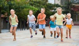 Groupe d'enfants de sourire courant ensemble dans la ville l'été Images stock