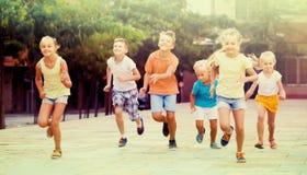 Groupe d'enfants de sourire courant ensemble dans la ville l'été Photographie stock libre de droits
